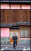 Bicyclist in front of a traditional style house. Kyoto, Japan