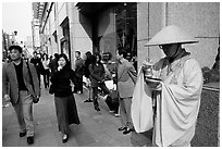 Buddhist monk seeking alms in front of a Ginza department store. Tokyo, Japan (black and white)