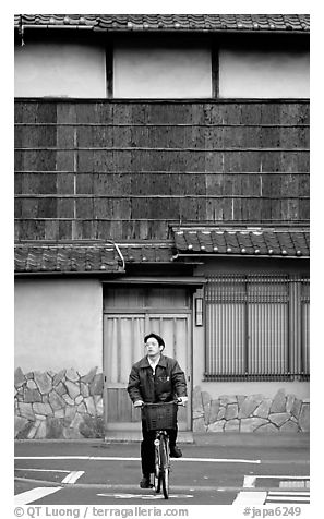 Bicyclist in front of a traditional style house. Kyoto, Japan (black and white)