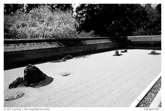 Ryoan-ji Temple has on of the most famous Zen gardens in the karesansui (dry landscape) style, a collection of 15 rocks in a sea of raked sand, enclosed by an earthen wall. Kyoto, Japan (black and white)