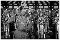 Some of the 1001 statues of the thousand-armed Kannon (buddhist goddess of mercy), Sanjusangen-do Temple. Kyoto, Japan ( black and white)