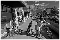 Woman and kids with mountain bikes on downtown Banff sidewalk. Banff National Park, Canadian Rockies, Alberta, Canada ( black and white)