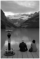 Couple sitting at the edge of Lake Louise at dawn. Banff National Park, Canadian Rockies, Alberta, Canada (black and white)