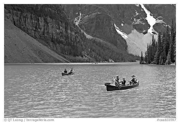 Canoes on the robbin egg blue Moraine Lake, afternoon. Banff National Park, Canadian Rockies, Alberta, Canada (black and white)