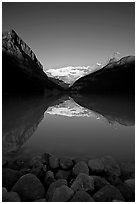 Boulders, Mirror-like Lake Louise and Victoria Peak, early morning. Banff National Park, Canadian Rockies, Alberta, Canada (black and white)
