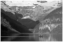 Rowers on Lake Louise, below Victoria Glacier, early morning. Banff National Park, Canadian Rockies, Alberta, Canada (black and white)