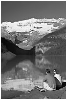 Couple sitting in the sun in front of Lake Louise, morning. Banff National Park, Canadian Rockies, Alberta, Canada (black and white)