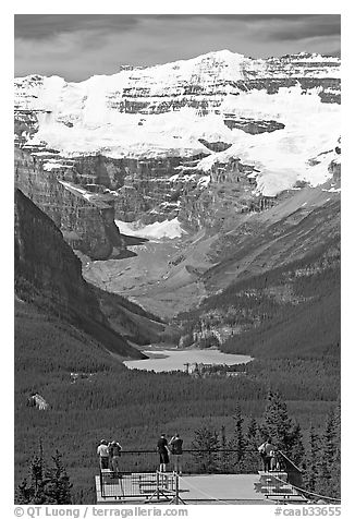 Tourists at observation platform, looking at  Lake Louise and  Victoria Peak. Banff National Park, Canadian Rockies, Alberta, Canada (black and white)