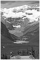 Tourists at observation platform, looking at  Lake Louise and  Victoria Peak. Banff National Park, Canadian Rockies, Alberta, Canada ( black and white)
