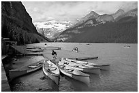 Red canoes at boat dock, Lake Louise, morning. Banff National Park, Canadian Rockies, Alberta, Canada (black and white)