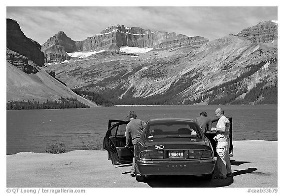 Tourists stepping out of a car next to Bow Lake. Banff National Park, Canadian Rockies, Alberta, Canada (black and white)