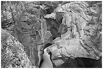 Narrow slot cut in limestone rock by river, Mistaya Canyon. Banff National Park, Canadian Rockies, Alberta, Canada (black and white)