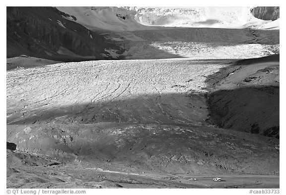 Base of Athabasca Glacier with cars parked on lot. Jasper National Park, Canadian Rockies, Alberta, Canada (black and white)