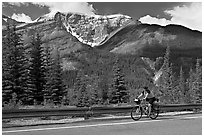 Woman cycling the Icefields Parkway. Jasper National Park, Canadian Rockies, Alberta, Canada (black and white)