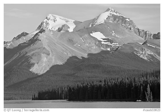Canoe dwarfed by the Mt Charlton and Mt Unwin surrounding Maligne Lake. Jasper National Park, Canadian Rockies, Alberta, Canada (black and white)