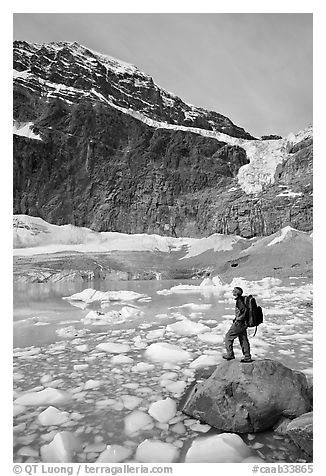 Hiker with backpack looking at iceberg-filed lake, glaciers, and mountain, Mt Edith Cavell. Jasper National Park, Canadian Rockies, Alberta, Canada (black and white)