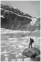 Hiker with backpack looking at iceberg-filed lake, glaciers, and mountain, Mt Edith Cavell. Jasper National Park, Canadian Rockies, Alberta, Canada ( black and white)