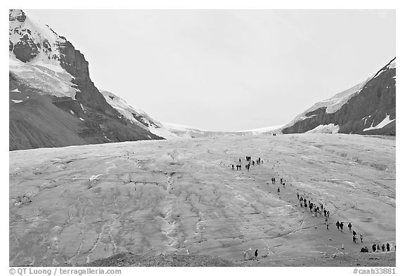 Toe of Athabasca Glacier with tourists in delimited area. Jasper National Park, Canadian Rockies, Alberta, Canada (black and white)