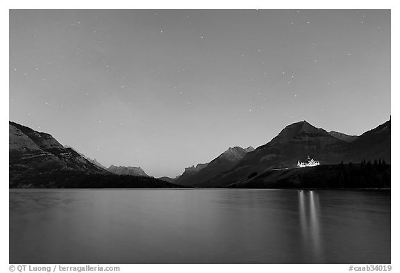 Waterton lake by night with stars in the sky in lights of Price of Wales Hotel. Waterton Lakes National Park, Alberta, Canada (black and white)