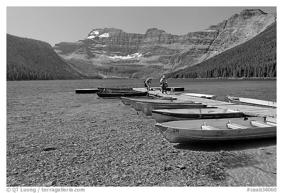 Fishermen walking on dock after unloading a canoe, Cameron Lake. Waterton Lakes National Park, Alberta, Canada (black and white)