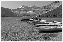 Fishermen walking on dock after unloading a canoe, Cameron Lake. Waterton Lakes National Park, Alberta, Canada ( black and white)