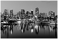 Fishing boats and skyline light reflected at night. Vancouver, British Columbia, Canada ( black and white)
