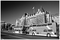 Red double-decker tour busses in front of Empress hotel. Victoria, British Columbia, Canada (black and white)