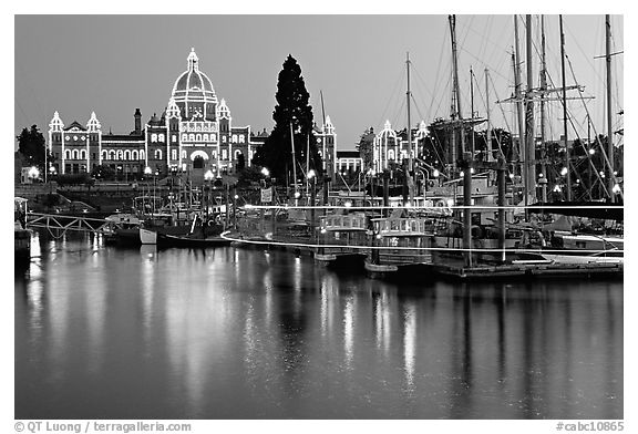 Boats in inner harbor with a trail of lights and parliament building lights. Victoria, British Columbia, Canada (black and white)