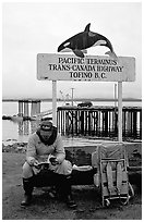 Backpacker sitting under the Transcanadian terminus sign, Tofino. Vancouver Island, British Columbia, Canada (black and white)