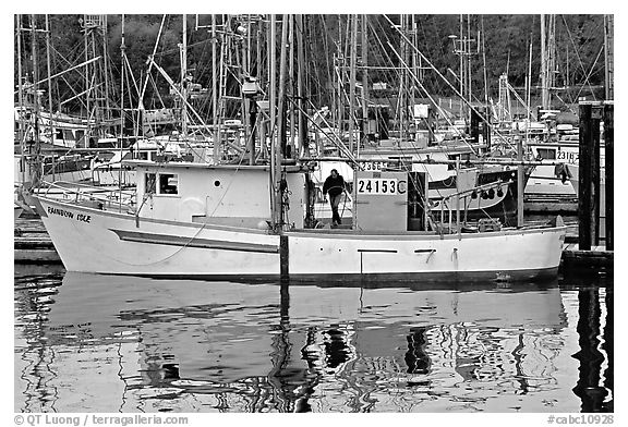 Fishing boat and reflections in harbor, Uclulet. Vancouver Island, British Columbia, Canada (black and white)