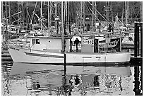 Fishing boat and reflections in harbor, Uclulet. Vancouver Island, British Columbia, Canada ( black and white)
