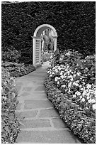 Arched entrance  leading to the Italian Garden. Butchart Gardens, Victoria, British Columbia, Canada ( black and white)