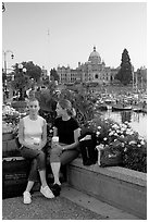 Women with shopping bags and coffee cups at the Inner Harbour, sunset. Victoria, British Columbia, Canada (black and white)