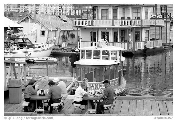 People eating fish and chips on deck,  Fisherman's wharf. Victoria, British Columbia, Canada (black and white)