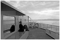 Passenger sitting on the deck of ferry. Vancouver Island, British Columbia, Canada ( black and white)