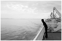 Woman looking out from deck of ferry. Vancouver Island, British Columbia, Canada ( black and white)