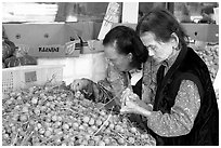 Two elderly women choosing tropical fruit. Vancouver, British Columbia, Canada (black and white)