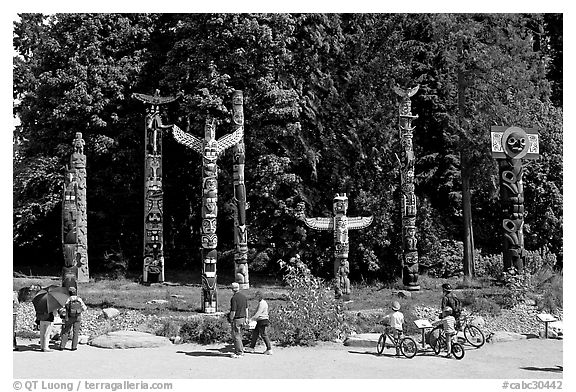 Tourists loooking at Totems, Stanley Park. Vancouver, British Columbia, Canada (black and white)