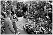 Women listening to the white parrot, Bloedel conservatory, Queen Elizabeth Park. Vancouver, British Columbia, Canada (black and white)