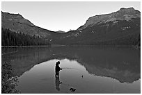 Woman fishing in Emerald Lake, sunset. Yoho National Park, Canadian Rockies, British Columbia, Canada ( black and white)