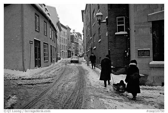 Residents pulling a sled with a child in a street, Quebec City. Quebec, Canada (black and white)