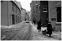 Residents pulling a sled with a child in a street, Quebec City. Quebec, Canada ( black and white)
