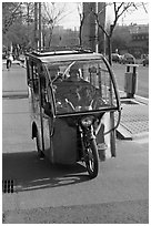 Enclosed three wheel motorcycle on street. Beijing, China ( black and white)