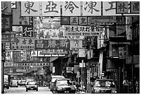 Taxicabs in a street filled up with signs in Chinese, Kowloon. Hong-Kong, China (black and white)