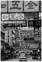 Busses in a street filled up with signs in Chinese, Kowloon. Hong-Kong, China ( black and white)