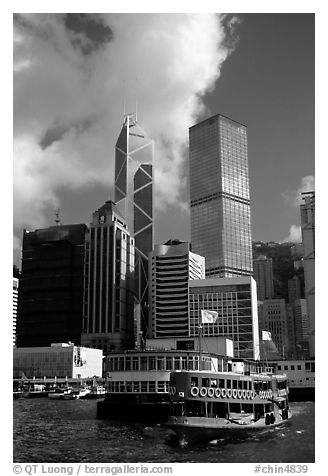 Ferry leaves a pier on Hong-Kong Island. Its symmetrical shape alleviates the need for turning around. Hong-Kong, China (black and white)