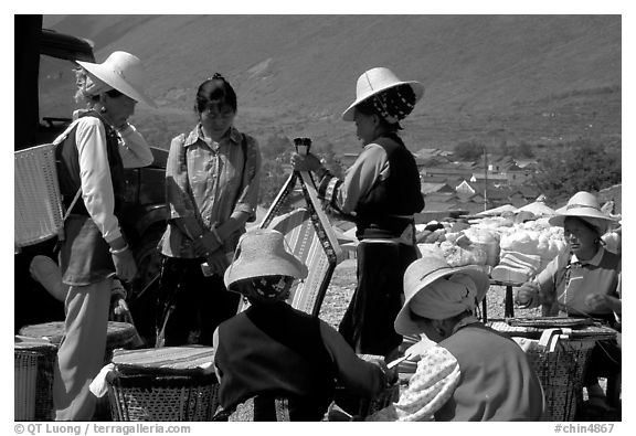 Bai women wearing tribespeople dress at the Monday market. Shaping, Yunnan, China (black and white)