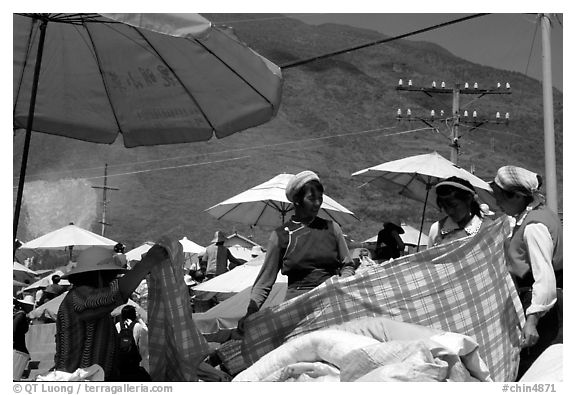 Bai women examining a piece of cloth at the Monday market. Shaping, Yunnan, China (black and white)