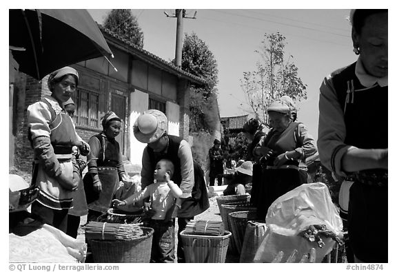 Women of Bai hill tribe offering incense for sale. Shaping, Yunnan, China (black and white)