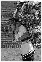 Woman carrying a load of chicken cages on forehead. Shaping, Yunnan, China (black and white)